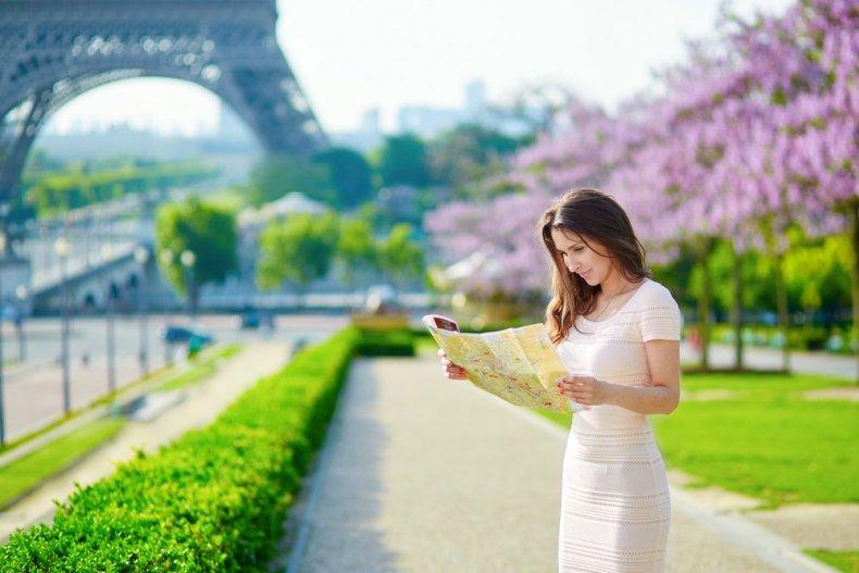 Женщина с картой вблизи Эйфелевой башни